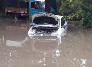 Припаркованная у обочины иномарка «утонула» на дороге после проливного дождя в Ростове