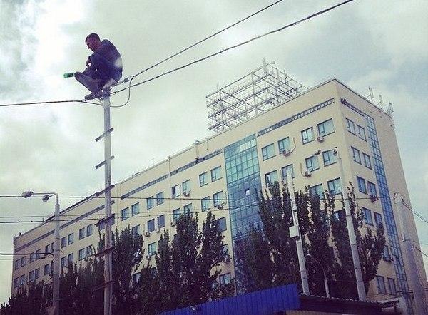 В Ростове мужчина залез на столб и угрожает покончить с собой. Видео
