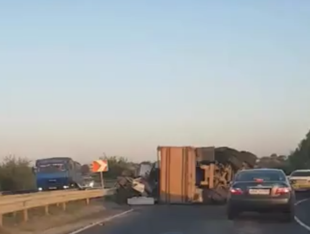 Перегруженный КамАЗ опрокинулся на съезде с моста под Ростовом на видео